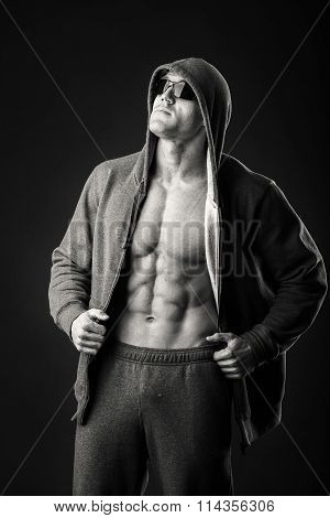 An athlete in a sports jacket with a hood on a dark background