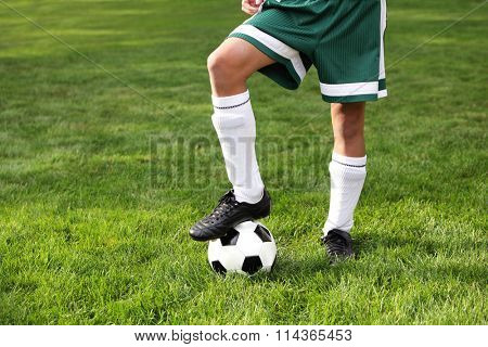 Close up of a boy's legs wearing cleets and ball