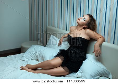 Woman In Dress Sitting On A Bed.