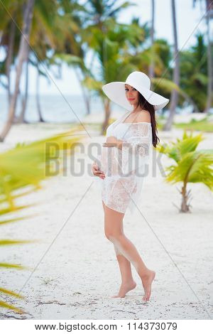Beautiful Pregnant Girl In White Dress And Wide-brimmed Hat On Beach Near Palm Trees