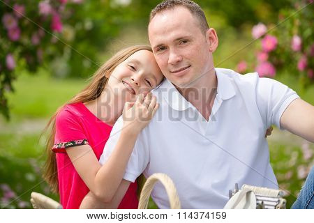 Beautiful Young Father And Small Pretty Daughter Embrace Outdoors