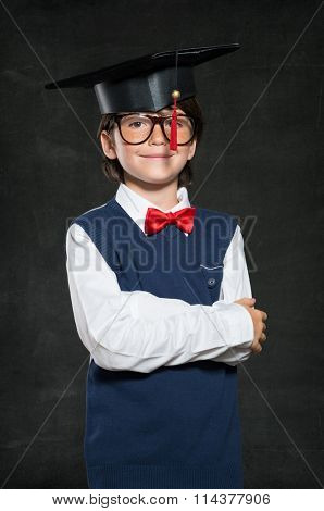 Closeup of smiling boy wearing mortar board against black background. Happy little boy achieve his scholar goals. Portrait of little graduated nerd looking at camera with pride.