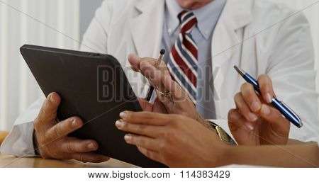Closeup Of Two Doctors Using A Tablet In The Office