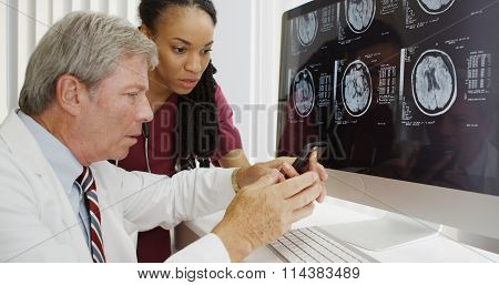 Two Doctors Analyzing Brain Xrays On Computer