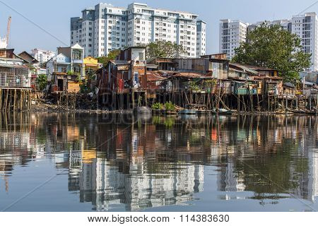 Views of the city's Slums from the river (in the background and in reflection of the new buildings) Ho Chi Minh City (Saigon), Vietnam.