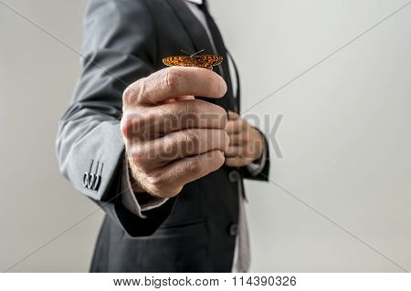 Butterfly On A Hand Of A Businessman In A Suit