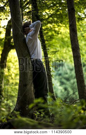 Businessman Standing Leaning On A Tree Trunk
