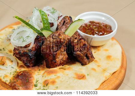 Shish kebab on pita bread, on a wooden spacing.