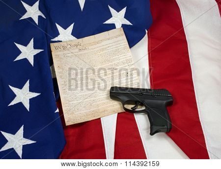 Constitution with Hand Gun on American Flag. Horizontal