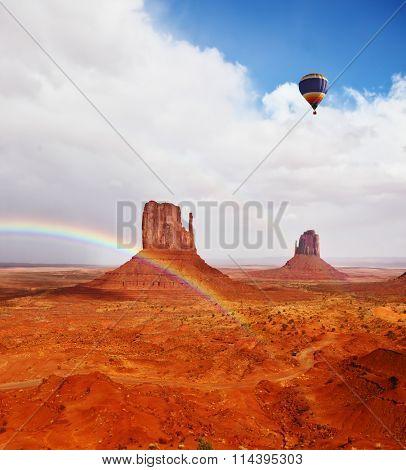 Huge balloon flies over Red Desert Navajo, USA. The picturesque rainbow crosses some rocks -