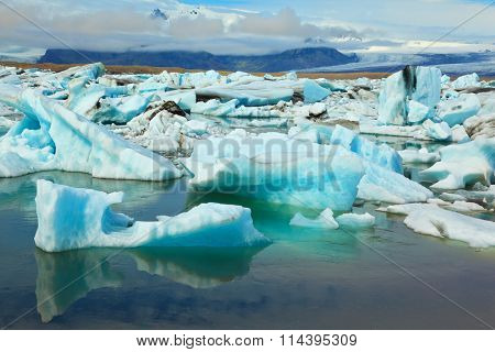 The blue and emerald icebergs and ice floes floating in the gulf Yokulsarlon in Iceland. Sunrise.