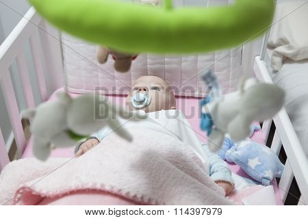 Baby Boy Lying In White Cot With Mobile