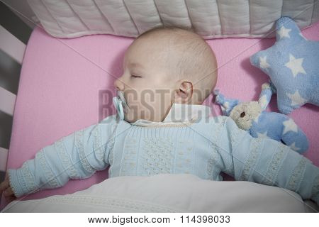 Sleeping Four Month Baby Boy Lying In Cot