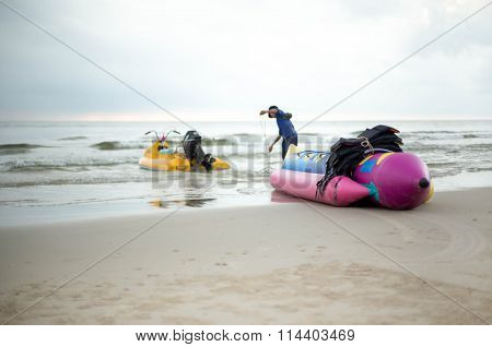 Unidentified Man Preparing His Banana Boat On The Beach