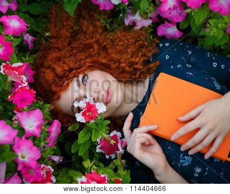 Red-haired Girl Lies In Wild Flowers.
