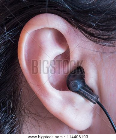Close up shot of a black earbud inside someone's right ear