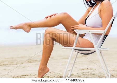 close up of woman sunbathing in lounge on beach