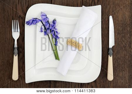 Table place setting with white porcelain dishes, bluebell flowers, antique cutlery and serviette with gold ring over old oak background.
