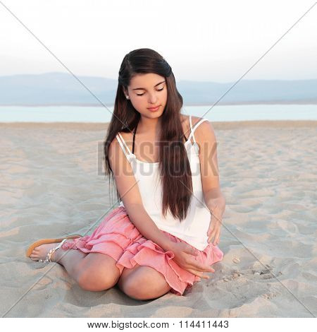 Young causcasian beautiful girl with long dark hair sitting on a beach and playing with sand.