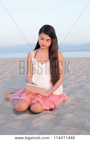 Beautiful young caucasian teenage girl with long dark hair on a tablet computer on a beach in summer.