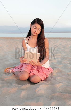Young teenage girl relaxing on a beach with a tablet computer device.