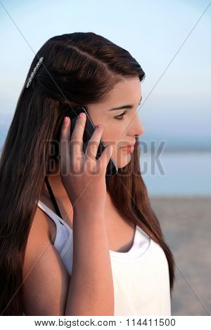 Beautiful young caucasian teenage girl with long dark hair on her cell phone.