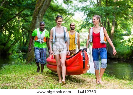 Friends carrying a canoe at river thru forrest