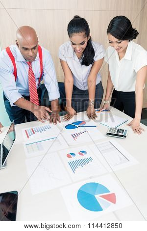 Asian business team in strategy meeting bowing on desk over with graphs and numbers