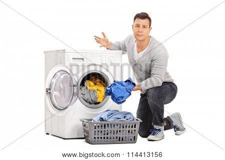 Sad young guy emptying a washing machine isolated on white background