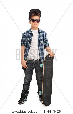 Full length portrait of a cool little skater boy with a cap and black sunglasses isolated on white background