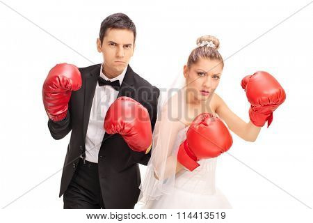 Studio shot of an angry newlywed couple posing with red boxing gloves isolated on white background