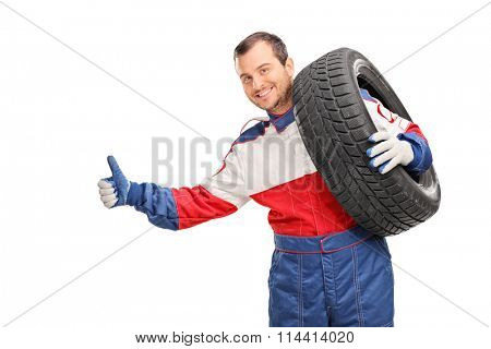 Young car racer carrying a tire on his shoulder and hitchhiking with his thumb isolated on white background
