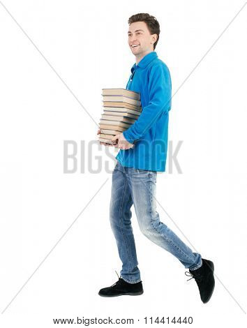 back view of going  man carries a stack of books. walking young guy . Rear view people collection.    Isolated over white background. The guy in a warm sweater carries a book with a broad smile.