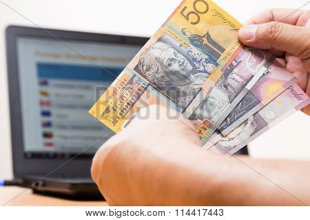 Hand Holding Australian Dollar In Office With Computer In Background