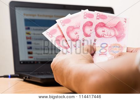 Hand Holding China Yuan In Office With Computer In Background