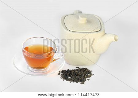 White teapot, a cup of tea and dried tea leaves.