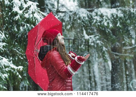 Profile portrait of romantic girl catching snowflakes with outstretched arm in winter outdoor during