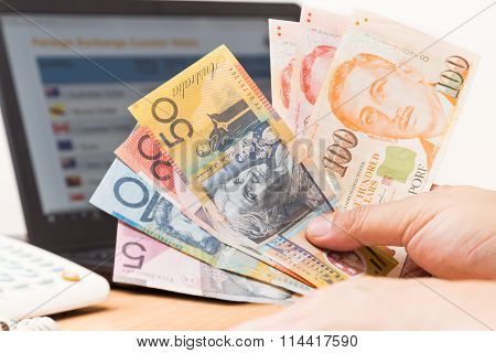 Hand Sorting Australian Dollar And Singapore Dollar With Computer Background