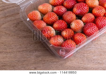 Red Ripe Strawberry In Plastic Box Of Packaging On Wood Table