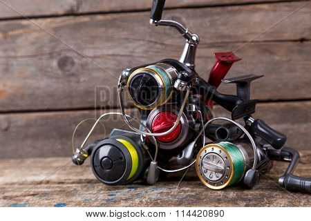 Different Fishing Reels With Line On Wooden Background