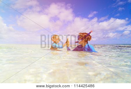 happy mother and son snorkeling on beach
