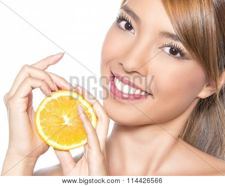 beautiful young asian woman with long hair and flawless skin holding orange. Isola