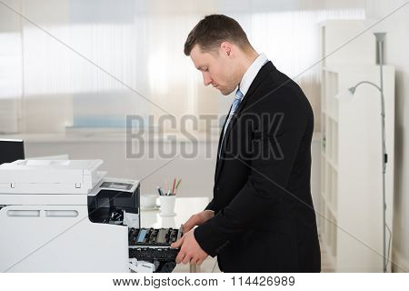 Businessman Adjusting Cartridge In Photocopy Machine