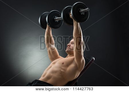 Determined Man Lifting Dumbbells While Reclining On Chair