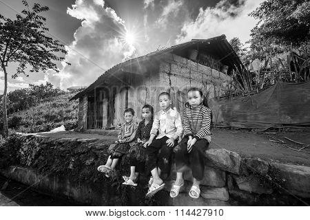 The children sitting on the doorstep