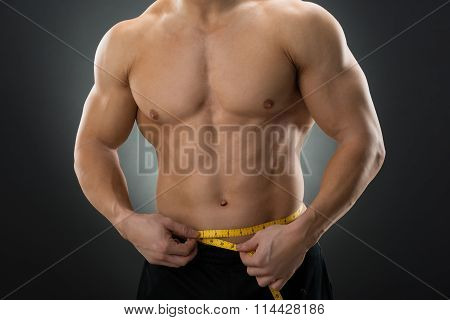 Midsection Of Muscular Man Measuring Waist