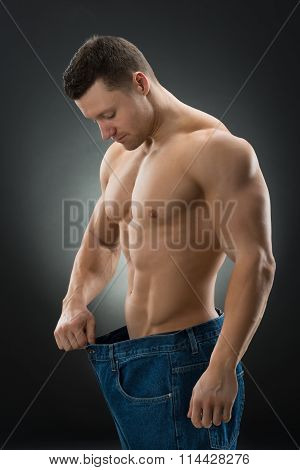 Muscular Man Showing Weight Loss By Wearing Old Jeans