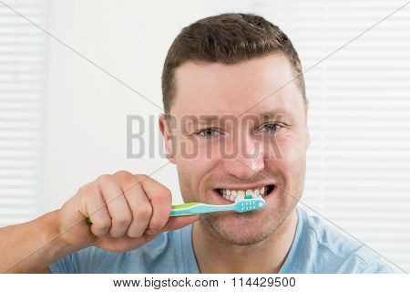 Man Brushing Teeth At Home