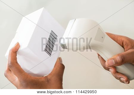 Person's Hand Using Barcode Scanner To Scan A Barcode