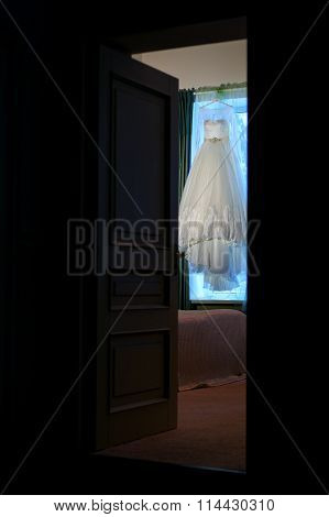 Beautiful wedding dress hanging in the doorway